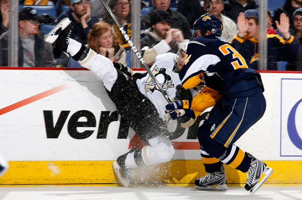 Tim Wallace #63 of the Pittsburgh Penguins is checked by Chris Butler #34 of the Buffalo Sabres on December 22, 2008 at HSBC Arena in Buffalo, New York.  (Photo by Rick Stewart/Getty Images) *** Local Caption *** Tim Wallace;Chris Butler