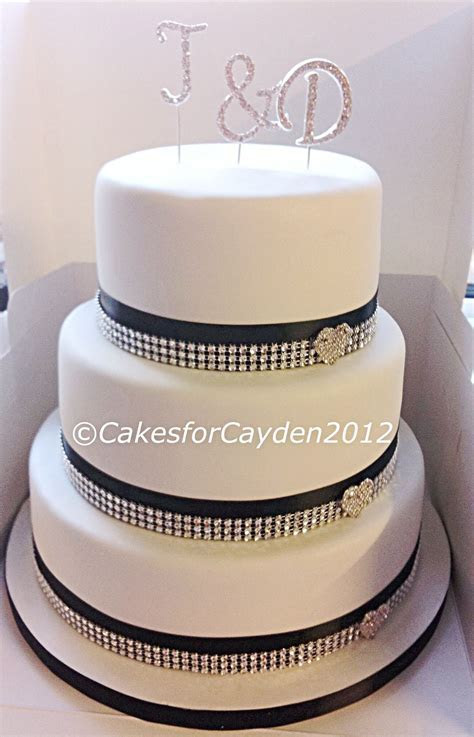 3 tier white wedding cake with black and bling ribbon