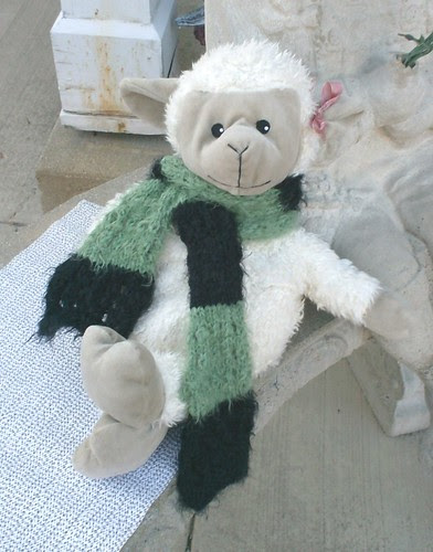 Stuffed sheep modeling a green and black striped handknit scarf