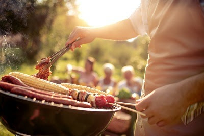 man barbecuing food items outdoors
