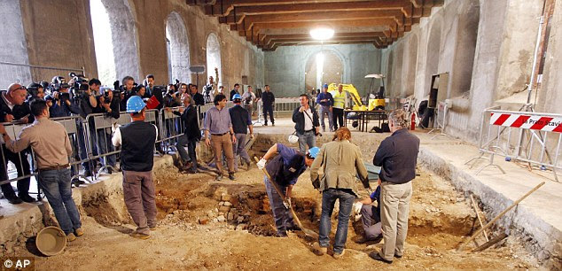 Cameras ready: researchers dig into the underground tombs inside the convent while a crowd of media watches for discoveries