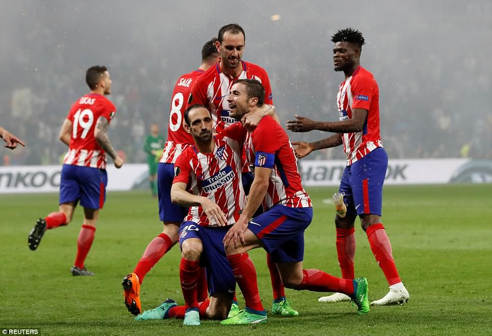 Atletico players celebrate together as their victory is sealed by a strike from their captain Gabi in the 89th minute