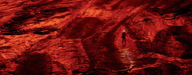 A scientist walks on the cooled lava floor of a volcano. (Carsten Peter/National Geographic)