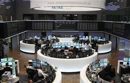 Traders are pictured at their desks in front of the DAX board at the Frankfurt stock exchange January 10, 2012. REUTERS/Lmar Niazman