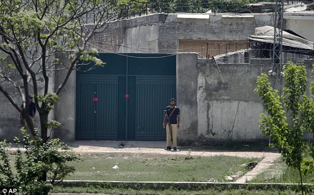 Empty: Two Pakistani police officers stand guard at the main gate of Bin Laden's deserted compound in Abbottabad, northwestern Pakistan today