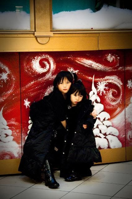 Mon Dec 19,2011, My girls - obliging me one capture in front of a gynormous Christmas display in downtown Montreal.