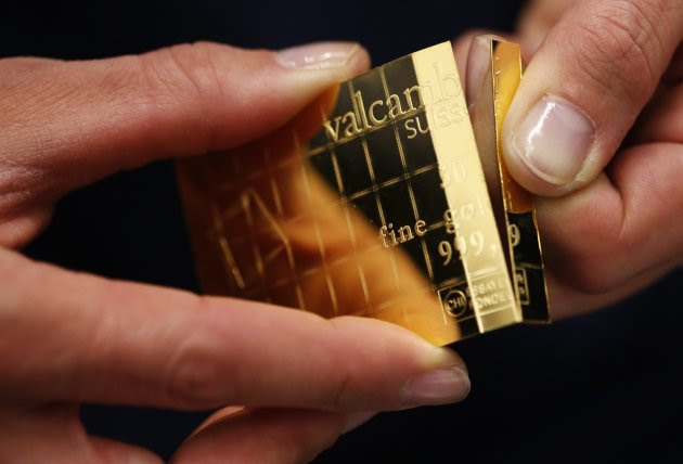An employee shows dividing a gold Combibar at a plant of gold refiner and bar manufacturer Valcambi SA in the southern Swiss town of Balerna