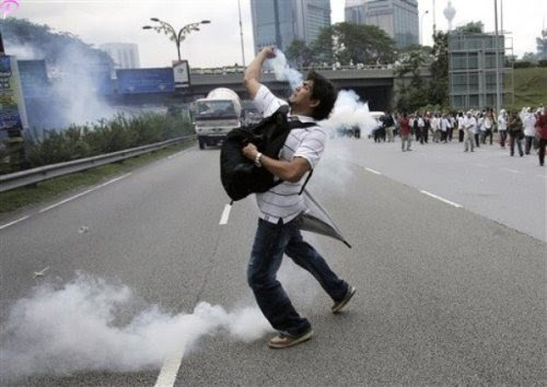 A protester throws back a tear gas which fired by riot police during a protest against using English for mathematics and science teaching in Kuala Lumpur, Malaysia, Saturday, March 7, 2009.AP Photo