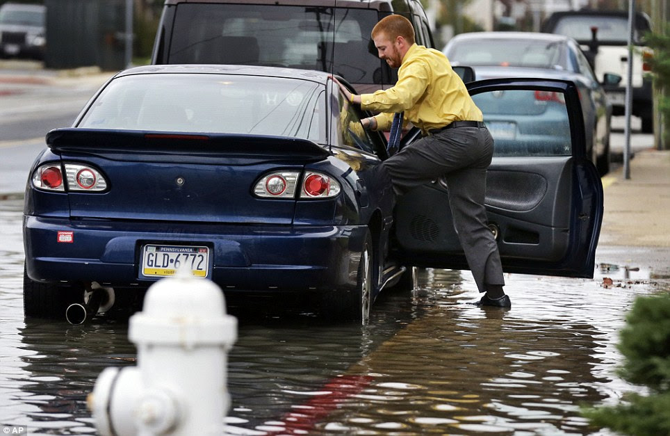 Cody Billotte walks through the high water as he loads his car to go to work as Hurricane Sandy bears down on the East Coast, Sunday, Oct. 28, 2012, in Ocean City, Maryland
