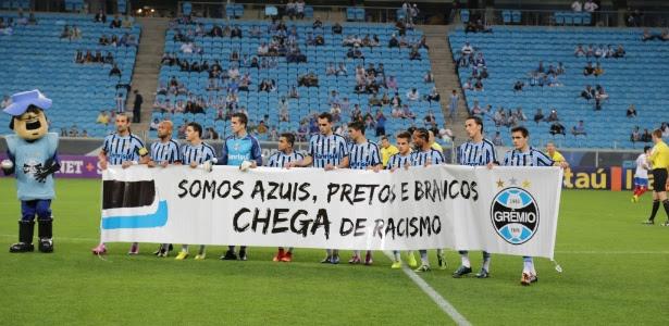 Jogadores do Grêmio entram em campo para o jogo com o Bahia com faixa contra o racismo