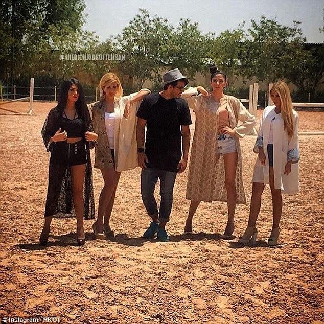 Aqui, um jovem é acompanhado por um grupo de jovens mulheres elegantes em uma paisagem empoeirada
