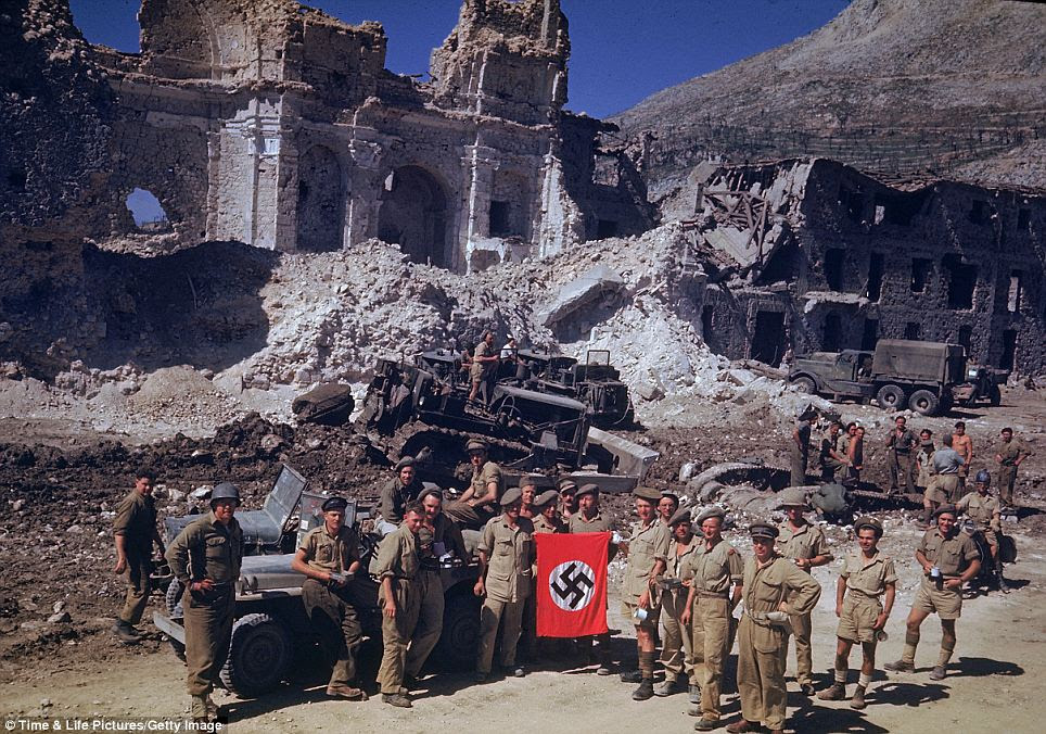 March to Rome: This May 1943 photo shows British and South African soldiers showing off a Nazi flag during the Allied march toward Rome in the Italian city of Cassino