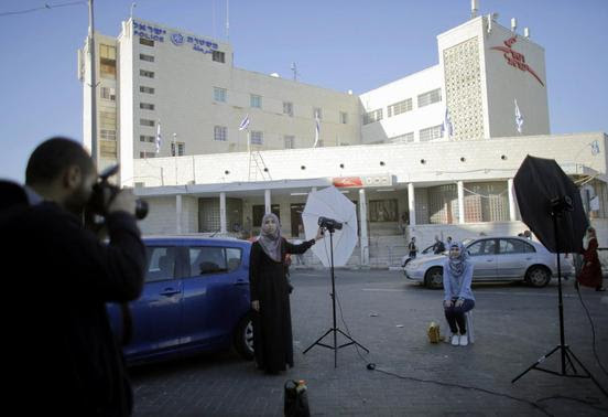 Palestinian students hold a photo shoot in front of a post office building in East Jerusalem April 29, 2014. REUTERS-Ammar Awad