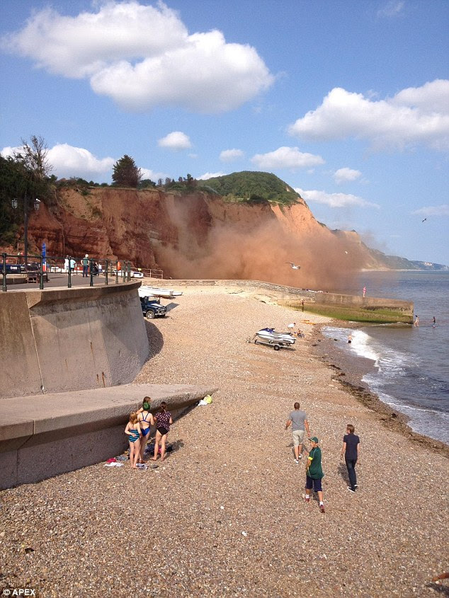 Landslide! Tourists move to safety on Sidmouth beach in Devon after part of the cliff comes crashing down