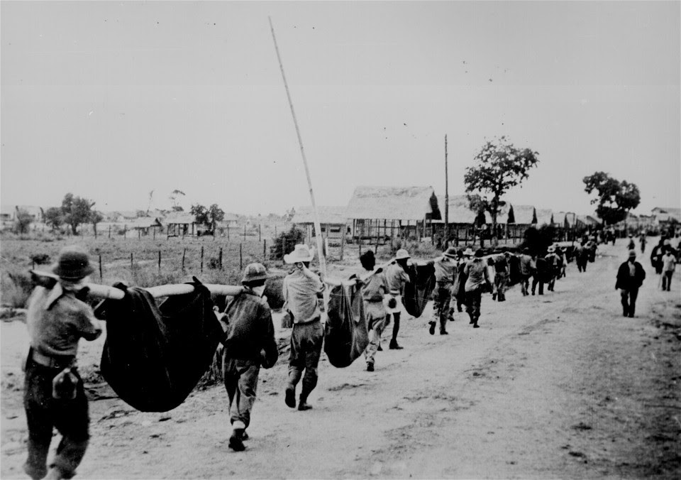 """This picture, captured from the Japanese, shows American prisoners using improvised litters to carry those of their comrades who, from the lack of food or water on the march from Bataan, fell along the road."" Philippines, May 1942. (Wikimedia Commons)"