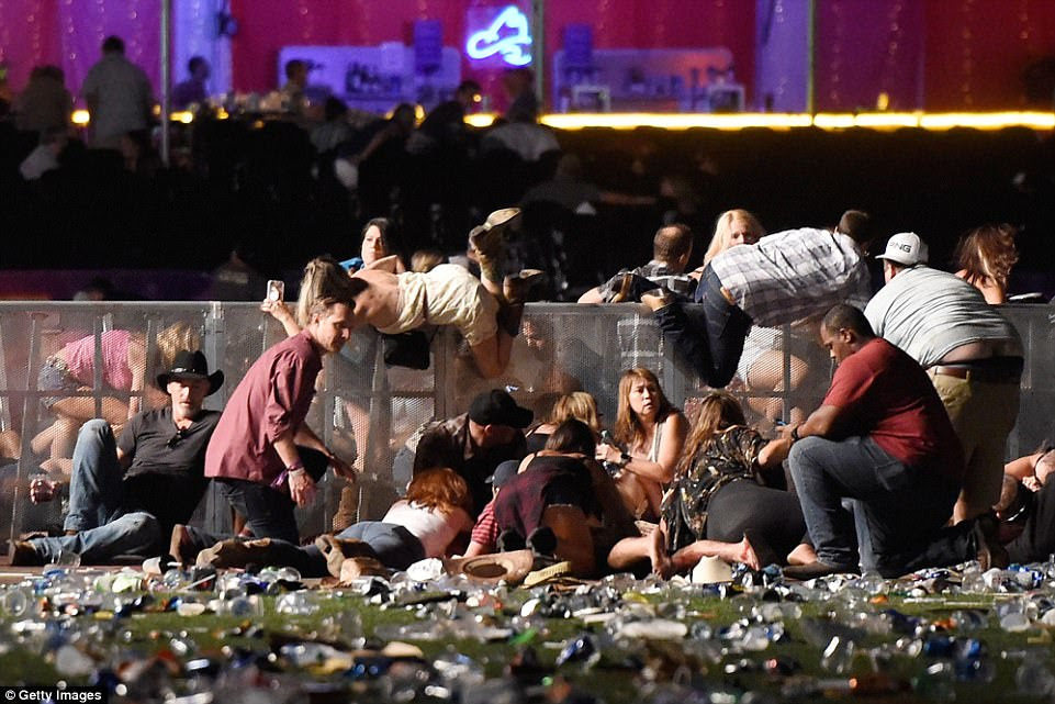 People scramble over barriers to get to safety as the gunfire rages on at the Las Vegas event