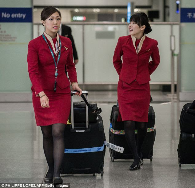 'Too sexy': Cathay Pacific flight attendants walk through Hong Kong International Airport. Their union has demanded that bosses redesign their uniforms, claiming that they have led to an increase in sexual harassment