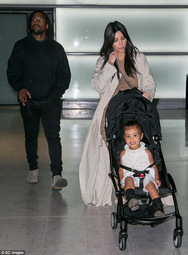 Someone's happy! North West wears a bright smile upon arriving in Paris with her parents