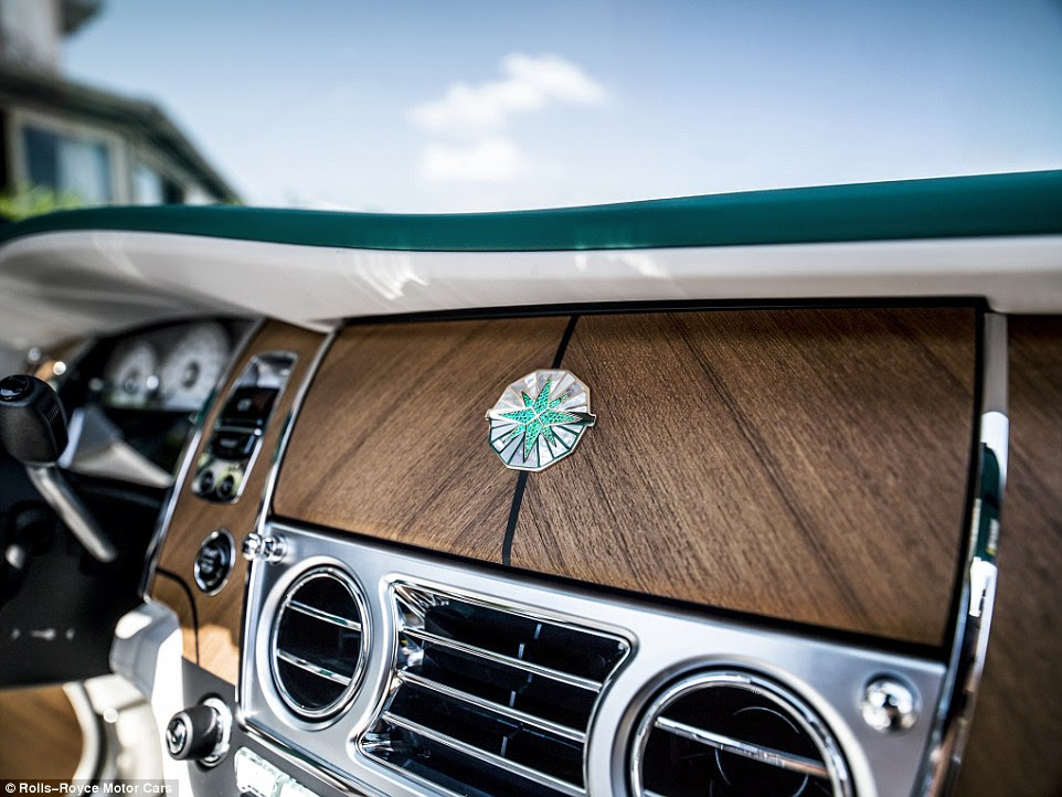This emblem fixed to the panel hiding the infotainment screen is Emerald stones and Mother of Pearl set in white gold