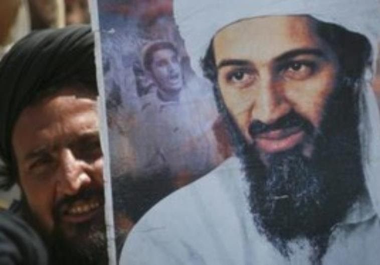 Man holds poster of Osama bin Laden at rally