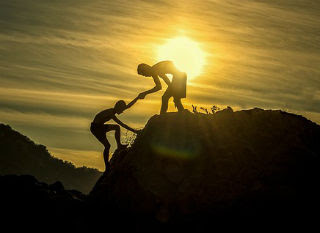 Man helping other person up a mountain