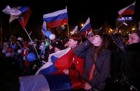 People celebrate and wave Russian flags as the preliminary results of today's referendum are announced in the Crimean city of Sevastopol March 16, 2014. REUTERS-Baz Ratner