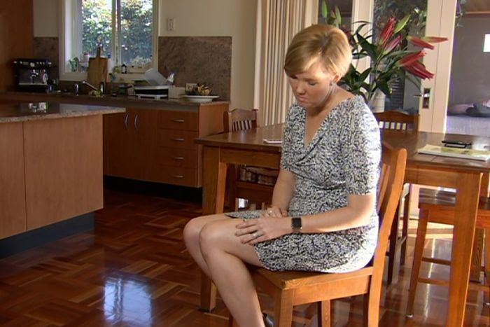 Rachel Argus sitting on a chair in her dining room showing where she had a melanoma removed from her leg. Oct 2017