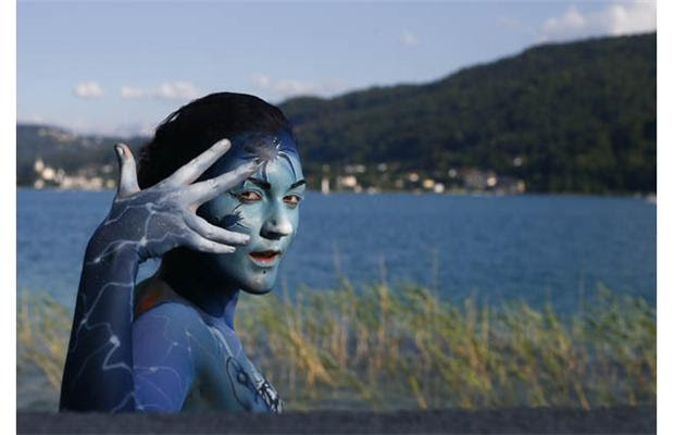 A participant poses with her body paintings during the 15th World Bodypainting Festival in front of the Woerthersee lake in Poertschach on July 7, 2012. Some 30,000 visitors are expected at the three-day event, with over 200 artists from 44 countries showing off their creations in the hope of taking home a prestigious World Award, the equivalent of a world championship title.