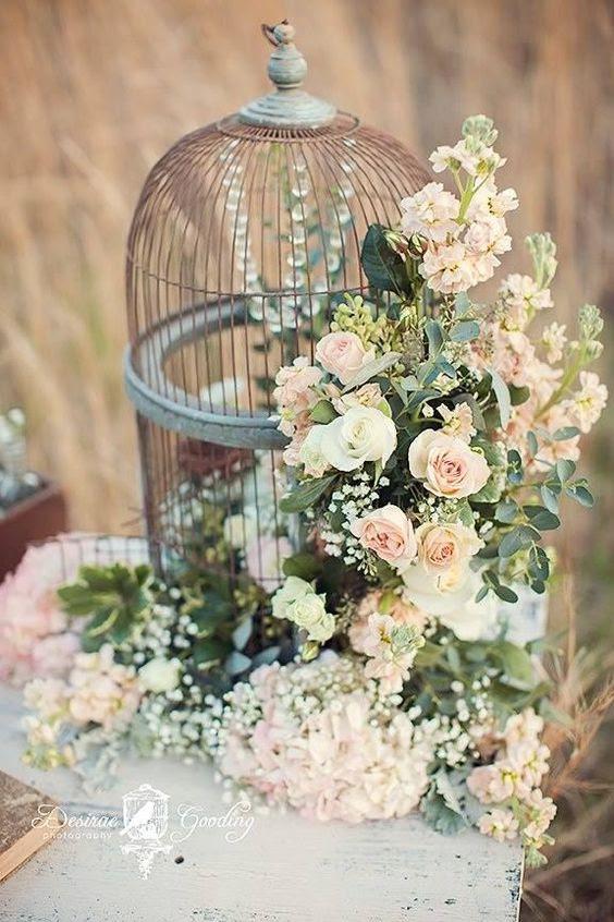 einen Vogelkäfig mit Kristallen im inneren und üppigen rosa Blüten und grün befestigt, die außerhalb