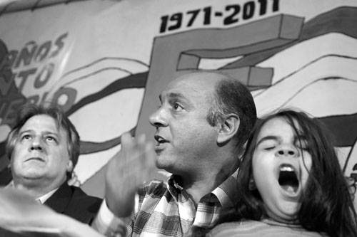 """Fernando Lorenzo, ministro de Economía y Finanzas, junto a Marcelo Abdala, coordinador del PIT-CNT, y su hija, durante la charla debate """"¿Hacia dónde va la economía nacional? El gobierno y los trabajadores debatimos juntos"""", en el comité Cuaró del Frente Amplio, en el barrio La Teja de Montevideo."""