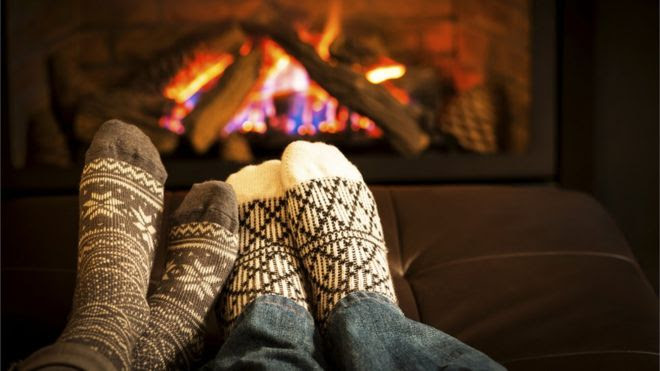 Two pairs of feet in socks in front of a roaring fire