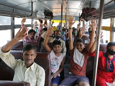 Migrants and their families, who arrived from Gujarat on a train, wave from inside a bus as they prepare to leave for their native villages in their home state of Uttar Pradesh. AP