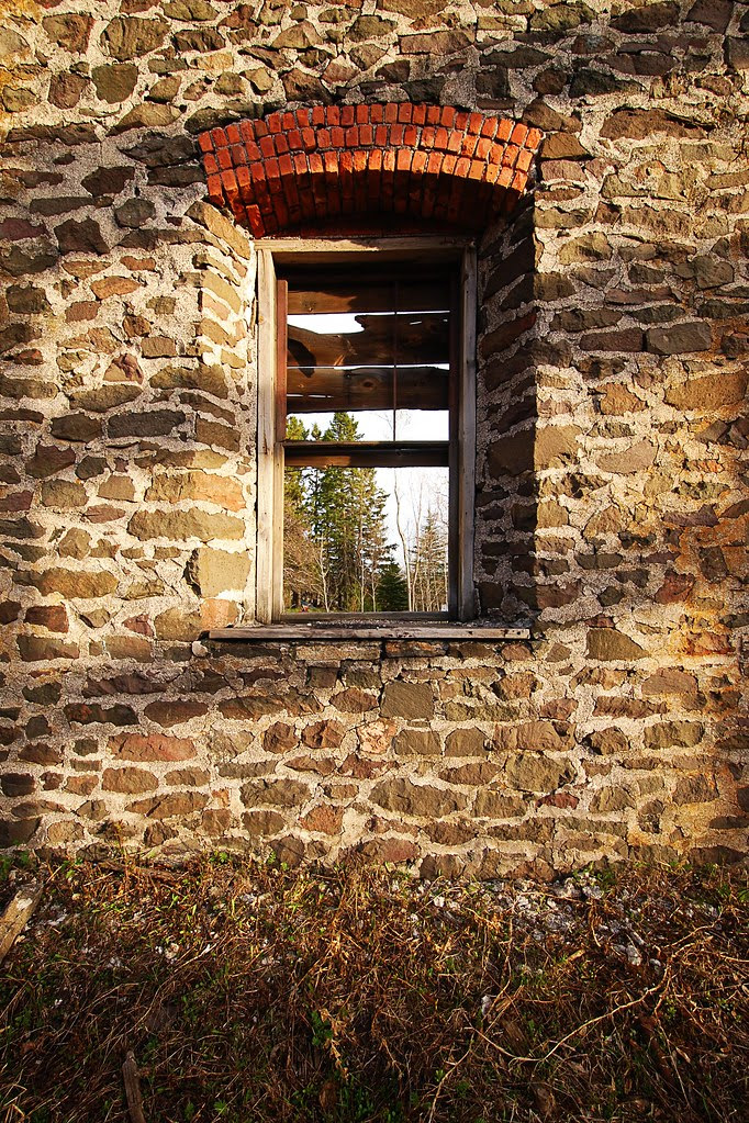A boarded up window in a stone wall.