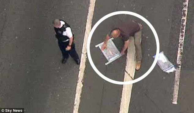 Evidence bags: Police forensic officers collect evidence from the scene in Woolwich, south-east London