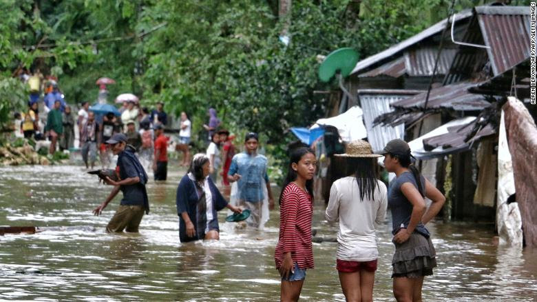 Villagers wade through a flooded street in Brgy Calingatngan, in Borongan, on easterm Samar in central Philippines on December 16, 2017.