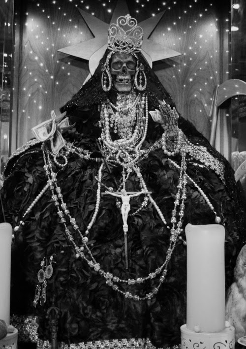 LA SANTA MUERTA The female grim reaper. The dark skeleton saint. She proudly sits on her throne with a crown tilted on her bony head. She loves her sacrifices. Sacrifices of humans—any humans. She will avenge your enemies and reward you with great wealth. Be evil and prosper.