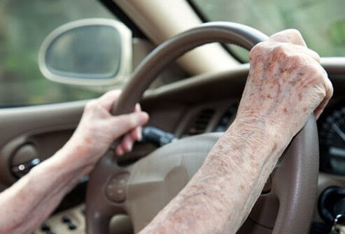 An elderly person's hands on the steering wheel.