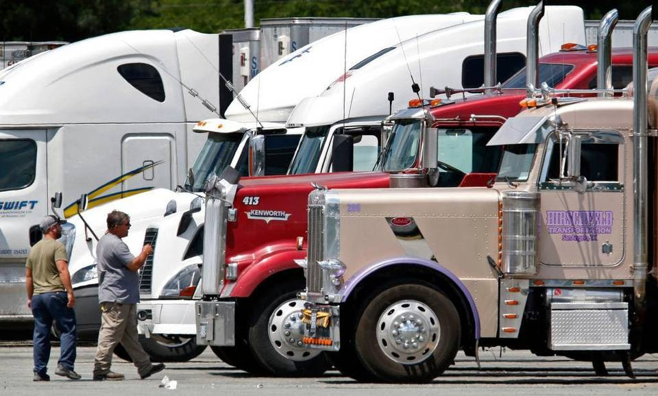 Drivers approach their semi-truck while parked in a rest area of the Truckstops of America Travel Center at the Highway 61 exit in Guilford County, NC Friday, June 5, 2015. This popular truck stop is on the busy I-40/85 interstate corridor through North Carolina.