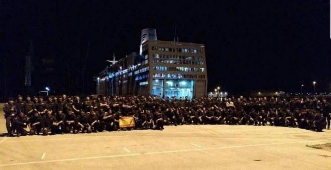 La Policía Nacional posando, con bandera de España incluida, al lado del crucero en el que se alojan en Barcelona. (@PortuariosCNT)