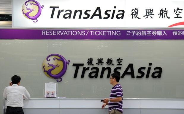 Jornalistas locais aguardam em frente a balcão da TransAsia no aeroporto de Sungshan, em Taipei, nesta quarta-feira (23), após um acidente com um avião da companhia que deixou dezenas de mortos (Foto: Sam Yeh/AFP)