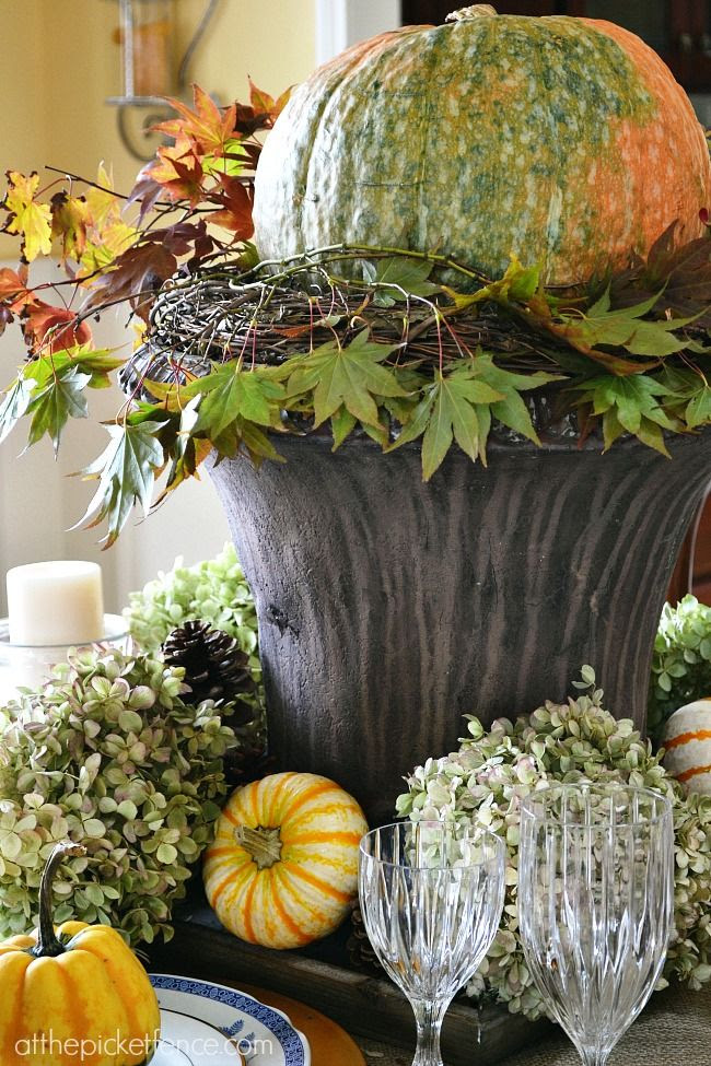 Natural fall centerpiece with pumpkins, hydrangeas and pine cones from atthepicketfence.com