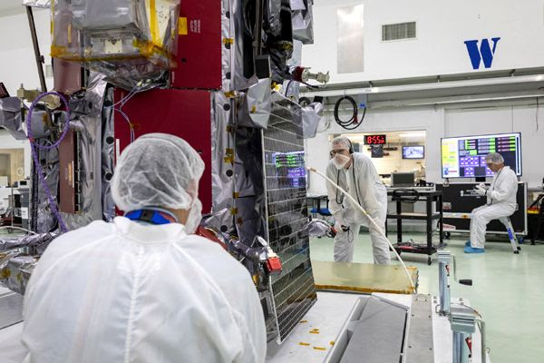 Parker Solar Probe team engineers inspect one of the twin solar arrays installed aboard the spacecraft on May 31, 2018...at Astrotech Space Operations in Titusville, Florida.