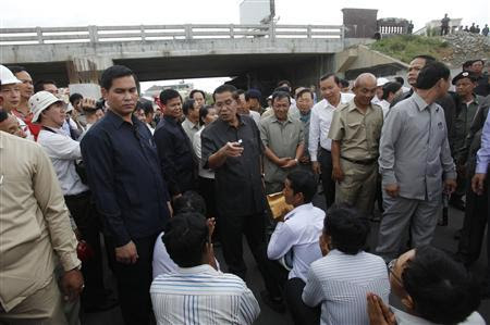 Cambodia's Prime Minister Hun Sen (C) speaks to workers as he inspects a bridge construction site in Phnom Penh July 31, 2013. REUTERS-Samrang Pring