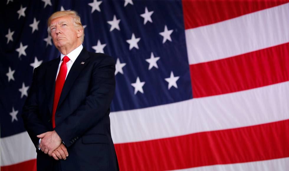 Donald Trump posa junto a una bandera de Estados Unidos