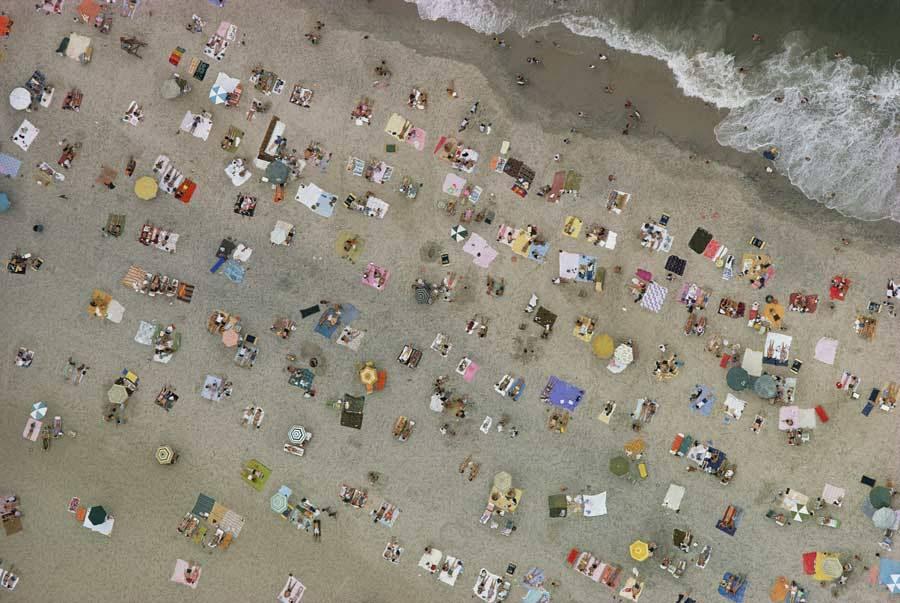 Vista aérea de bañistas acampados junto al mar en las toallas de playa o bajo las sombrillas en Ocean City, Maryland.Photograph por Emory Kristof, National Geographic