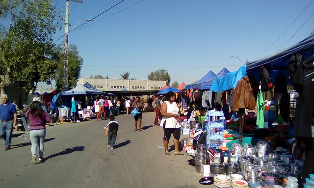 Every Sunday, on Pingüinos street, there is a street fair where Haitian migrants go to buy clothes, shoes and a variety of products, including some from their own country, and where they eat typical dishes from Haiti, offered at different stands. Credit: Orlando Milesi / IPS