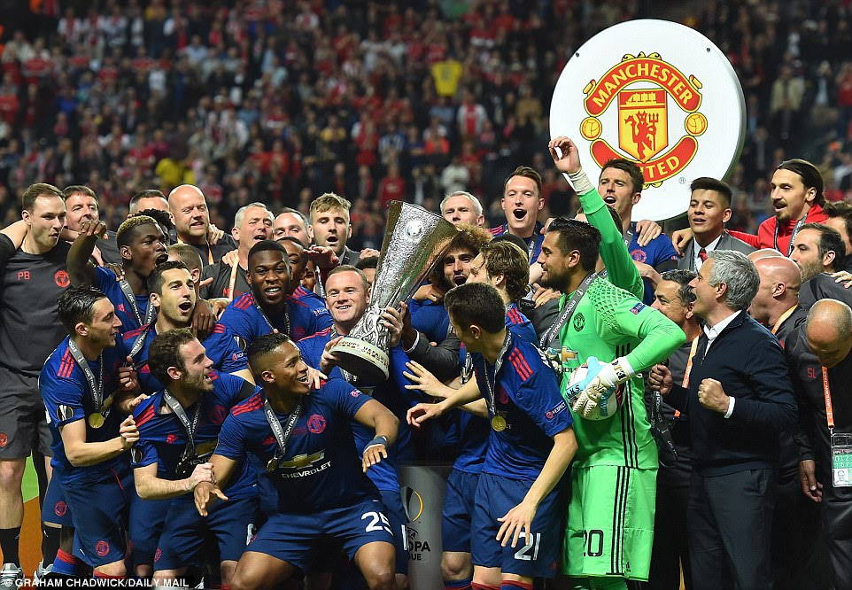 United captain Wayne Rooney, who came on as a substitute, holds the trophy as his team celebrate their latest triumph