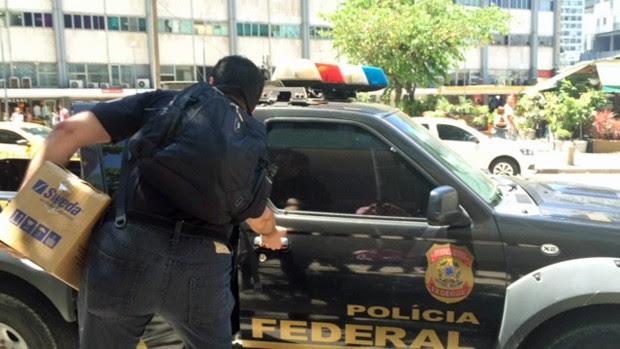Policial Federal deixa prédio do escritório de Eduardo Cunha, no Centro do Rio, carregando caixa (Foto: Matheus Rodrigues/G1)