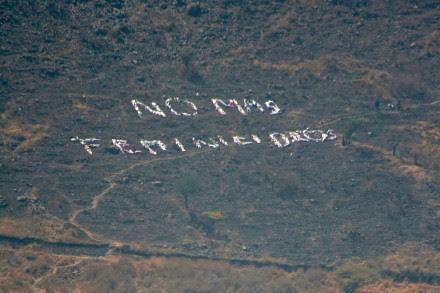 """Mujeres forman la leyenda """"No más feminicidios"""" en el cerro de Tepeolulco, Edomex. Foto: Hugo Cruz"""