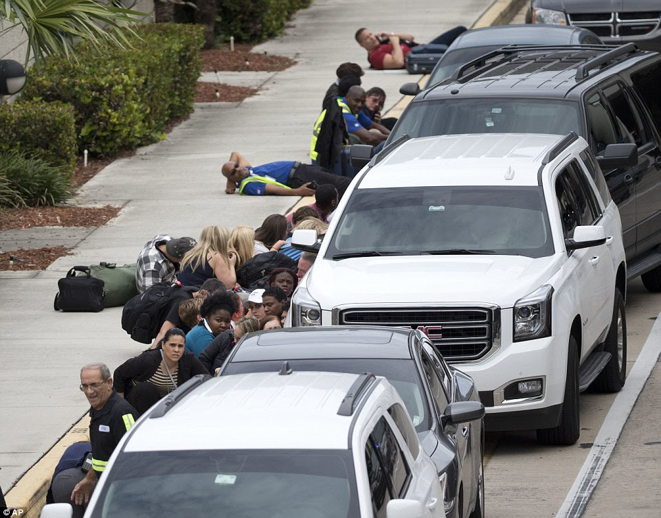 People take cover outside Fort Lauderdale-Hollywood International Airport, Friday, Jan. 6